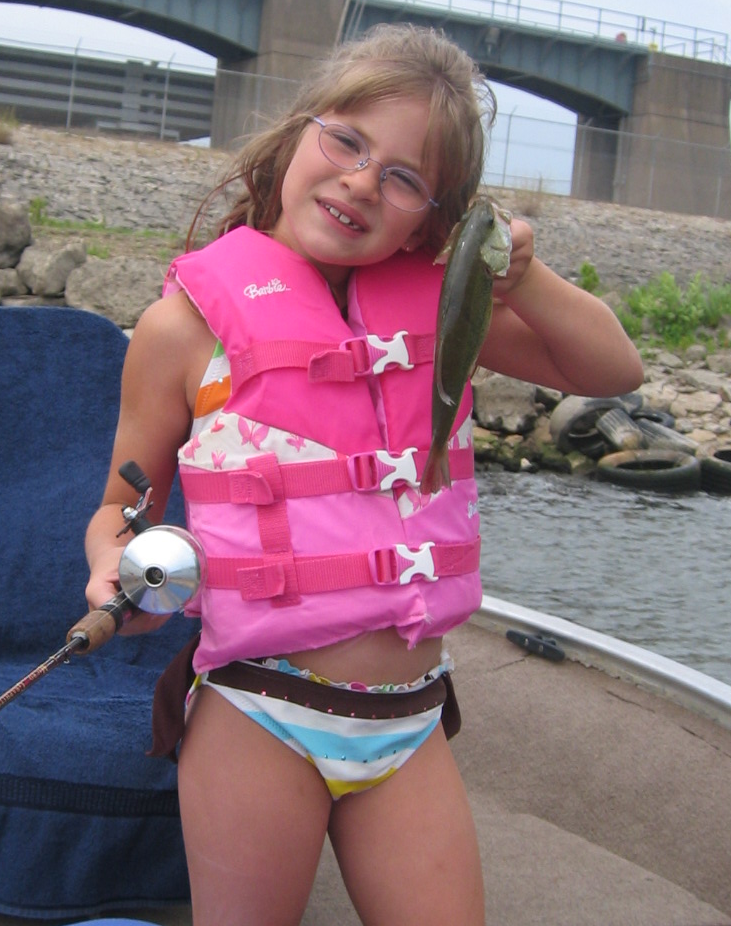 little girl holding up fish